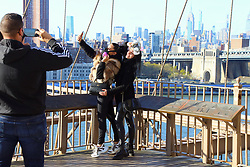 Tourists with face mask on the Brooklyn Bridge during the Covid-19 pandemic in New York City, NY, USA on April 22, 2020. The Big Apple neared a painful milestone Wednesday as the death toll from the coronavirus outbreak that has ravaged the five boroughs approached 15,000. The pandemic has claimed the lives of 14,996 New Yorkers, with new 569 fatalities reported in the most recent 24-hour period, according to data from the city's Department of Health. Photo by Charles Guerin/ABACAPRESS.COM