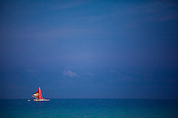 Sailboat with red sail on the bay just off White Sand Beach, Boracay, Philippines.