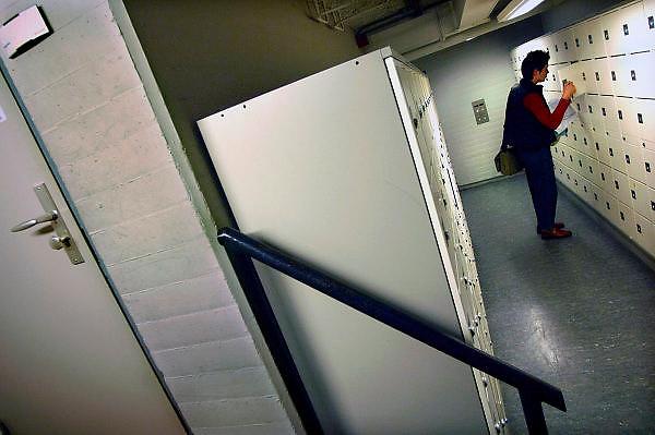 Nederland, Nijmegen, 16-7-2005..Verpleegkundige pakt in de nacht haar spullen uit een locker,afsluitbaar kastje,kluisje, in het..ziekenhuis UMC Radboud. Nachtdienst, veiligheid, angst, gevoel van onveiligheid, donker, onzeker, openbaar gebouw, diefstal, criminaliteit...Foto: Flip Franssen