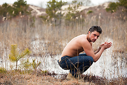 shirtless man by a pond in The Hamptons