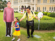 10 JANUARY 2015 - BANGKOK, THAILAND: A man and his daughter pose with a life sized cardboard cutout of General Prayuth Chan-ocha, the Prime Minister of Thailand during Children's Day festivities at Government House. National Children's Day falls on the second Saturday of the year. Thai government agencies sponsor child friendly events and the military usually opens army bases to children, who come to play on tanks and artillery pieces. This year Thai Prime Minister General Prayuth Chan-ocha, hosted several events at Government House, the Prime Minister's office.    PHOTO BY JACK KURTZ