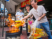 """10 AUGUST 2014 - BANGKOK, THAILAND: Men pour """"joss paper"""" into a burn barrel on the first day of Ghost Month in Bangkok. Joss paper also known as ghost money, are sheets of paper and/or paper-crafts made into burnt offerings. The seventh month of the Chinese Lunar calendar is called """"Ghost Month"""" during which ghosts and spirits, including those of the deceased ancestors, come out from the lower realm. It is common for Chinese people to make merit during the month by burning """"hell money"""" and presenting food to the ghosts.    PHOTO BY JACK KURTZ"""