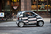Man driving a Smart Car in London. This microcar design was devised to be economic in terms of energy and space in a city environment.