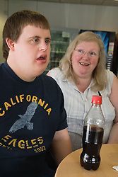 Student with Downs Syndrome and staff taking a break from lessons at special school,