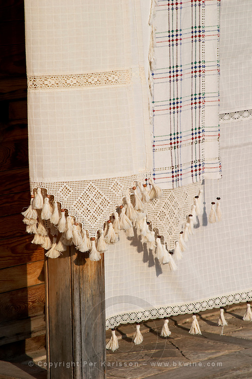 The busy old market bazaar street Kujundziluk with lots of tourist craft and art shops and street merchants. Traditional embroidered cloth and craft tissue. Detail of lace border. Historic town of Mostar. Federation Bosne i Hercegovine. Bosnia Herzegovina, Europe.
