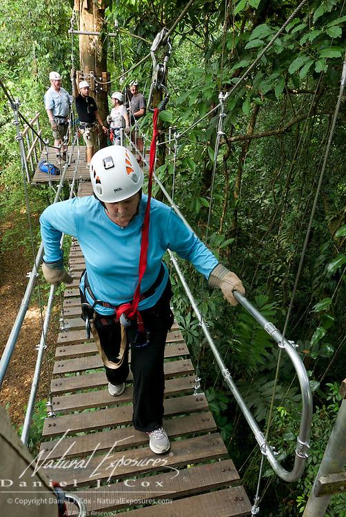 Carol on suspension bridge during zip line run. Costa Rica.