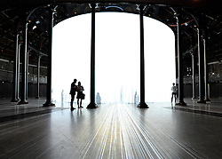 © licensed to London News Pictures. LONDON, UK.  08/08/11. People interact with Waking Dream. Ron Arad's Curtain Call opens at the Roundhouse, Camden in London today (9th August 2011). Arad has installed a huge light curtain made of 5,600 silicon rods, suspended from an 18 metre diameter ring. Films, live performance and audience interaction can all take place within and around the rods. Mandatory Credit Stephen Simpson/LNP