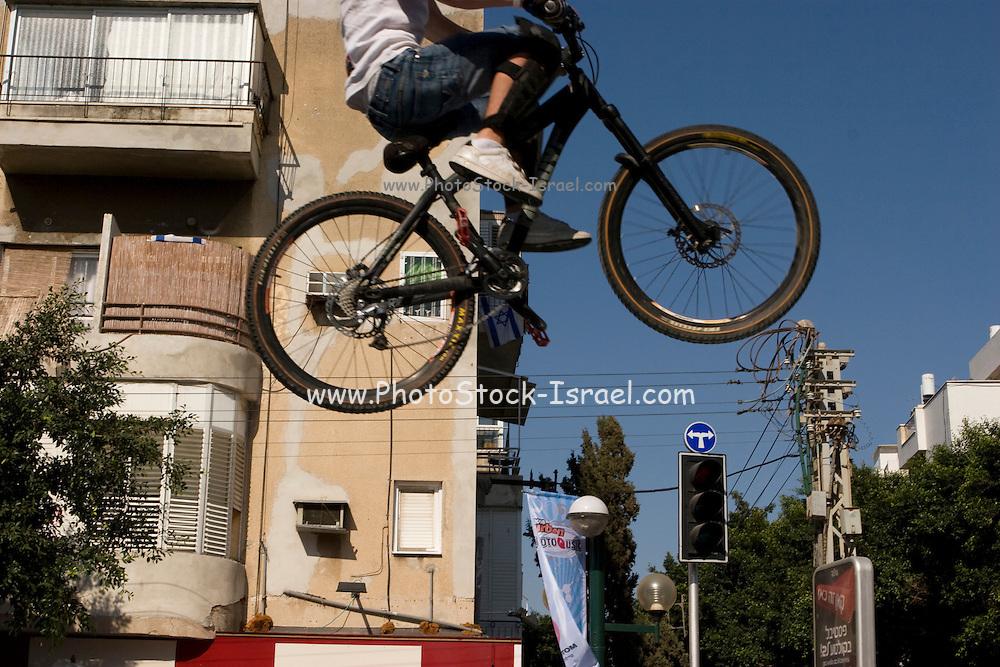 Israel, Tel Aviv, Bicycle stunt at an urban street party in Dizengoff street