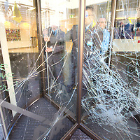 LONDON, ENGLAND - SEPTEMBER 08:  a Security guard behing a door and windows been smashed at Axa building in the City of London. Protestors targeted buildings of major corporations and banks, on September 8, 2009 in London, England.  (Photo by Marco Secchi/Getty Images)