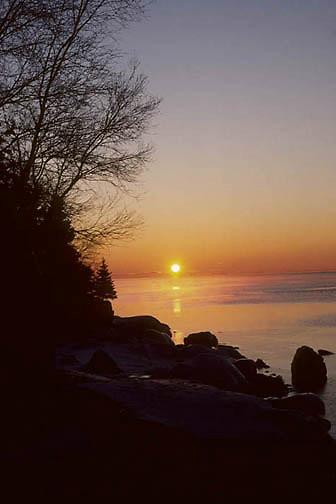Lake Superior, morning sun rises above horizon of Lake Superior's shoreline. Winter. Minnesota.