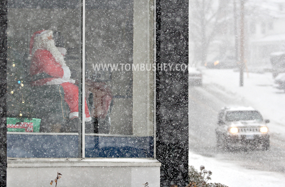 Middletown, NY - A mechanical Santa waves from the window of a store as cars drive by during a winter storm on Dec. 19, 2008.