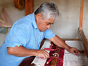 Amado Gutierrez Ruiz weaving a woollen rug with naturally dyed wool in the Zapotec weaving village of  Teotitlan del Valle in Oaxaca, Mexico on 29 November 2018