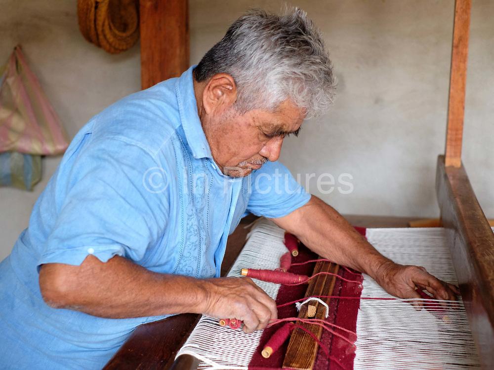 Amado Gutierrez Ruiz weaving a woollen rug with naturally dyed wool in the Zapotec weaving village of  Teotitlan del Valle in Oaxaca, Mexico on 29 November 2018