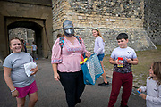 A woman wears a replica knight helmet after visiting the gift shop inside Dover Castle, United Kingdom on the 26th of August 2020. COVID restrictions around Dover Castle mean that visitors are required to  wear face coverings in certain parts of the castle. Dover Castle is a medieval castle high on the hill overlooking Dover and the English Channel, it has been a significant part of British history for the past 9 centuries and is now a UK tourist attraction run by English Heritage.