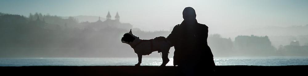 Silhouette of man and his dog sat on balaustrade in San Sebastian (Spain)