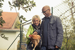 Senior couple holding a chicken bird in farm, Bavaria, Germany