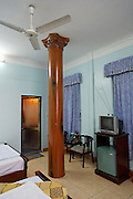 A wood effect Corinthian column in the middle of a hotel room, Cat Ba Town, Cat ba Island, vietnam