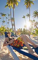 Teenage girl relaxes in a lounge chairs in a grove of Palm trees at Bavaro Beach, a popular tourist destination in the Dominican Republic.
