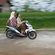 Two women riding a motorbike. Java, Indonesia.