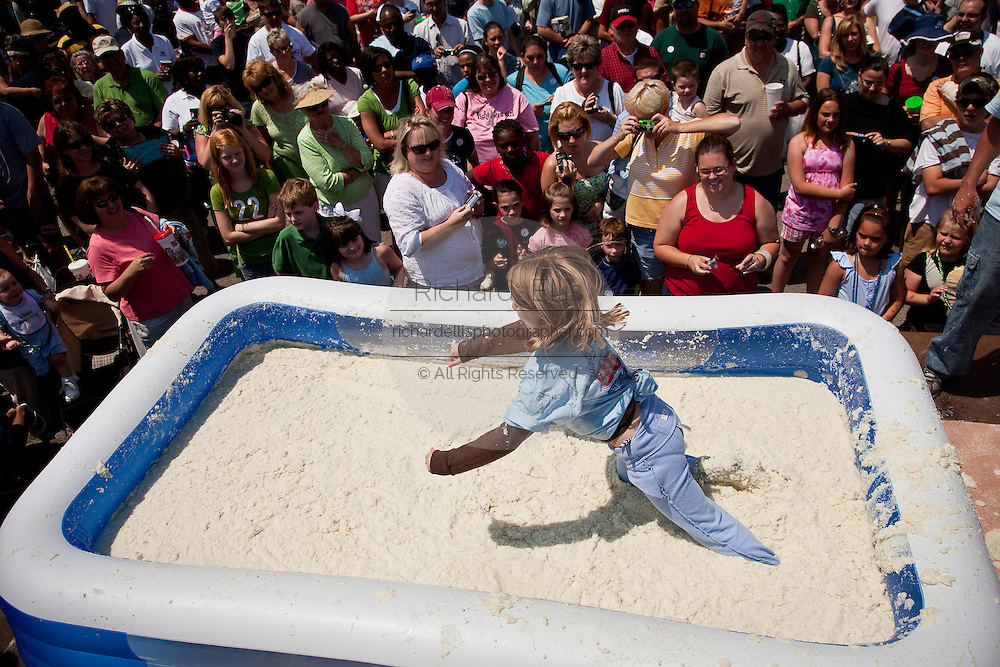 ST GEORGE, SC - APRIL 17: A young girl dives into a giant vat of grits during the World Grits Festival April 17, 2010 in St. George, South Carolina. Among the various events for the festival is the Rolling in the Grits for children where the winner is the one who can hold the most of grits to their body. Grits is corn-based porridge common in the Southern United States.   (Photo Richard Ellis)