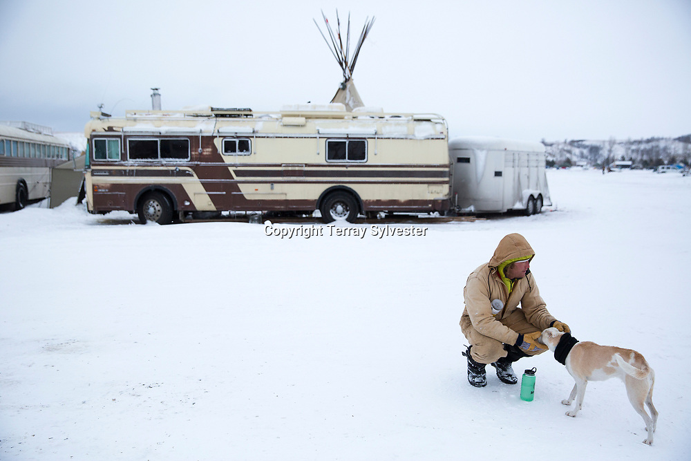 An opponent of the Dakota Access oil pipeline pets his dog in the pipeline opposition camp on November 30, 2016. Cannon Ball, North Dakota, United States.