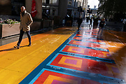 Londoners walk across a multicoloured pedestrianised traffic-free street in the City of London, capital's financial district, aka The Square Mile, on 20th October 2021, in London, England.