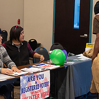 Rosa Revollo, left and Charlotte Blackgoat, center, from Somos Gallup welcome people to the Native Voters Right Forum Thursday evening at the El Morro Event Center and offer to help them register to vote.