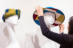 """© Licensed to London News Pictures. 05/04/2019. LONDON, UK. A gallery assistant adjusts a creation at """"The Great Hat Exhibition - World Garden"""", which is taking place at the Menier Gallery near London Bridge until 12 April 2019, as part of London Hat Week.  150 international milliners have created 200 hats inspired by the colours, flowers, plants and landscapes from around the world.  The exhibition is curated by Monique Lee Millinery and supported by X Terrace, a fashion platform.  Photo credit: Stephen Chung/LNP"""