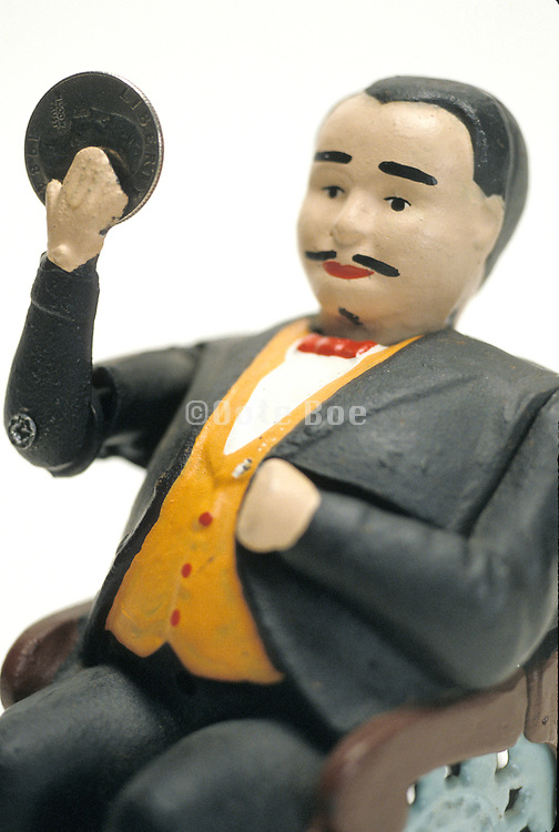 doll figure of man in suit waving with money