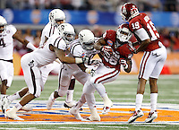 Oklahoma Sooners running back Damien Williams (26) is tackled by a host of Texas A&M Aggie defenders during the 77th AT&T Cotton Bowl Classic between the Texas A&M University Aggies and the Oklahoma University Sooners at Cowboys Stadium in Arlington, Texas. Texas A&M wins the 77th AT&T Cotton Bowl Classic against Oklahoma, 41-13.