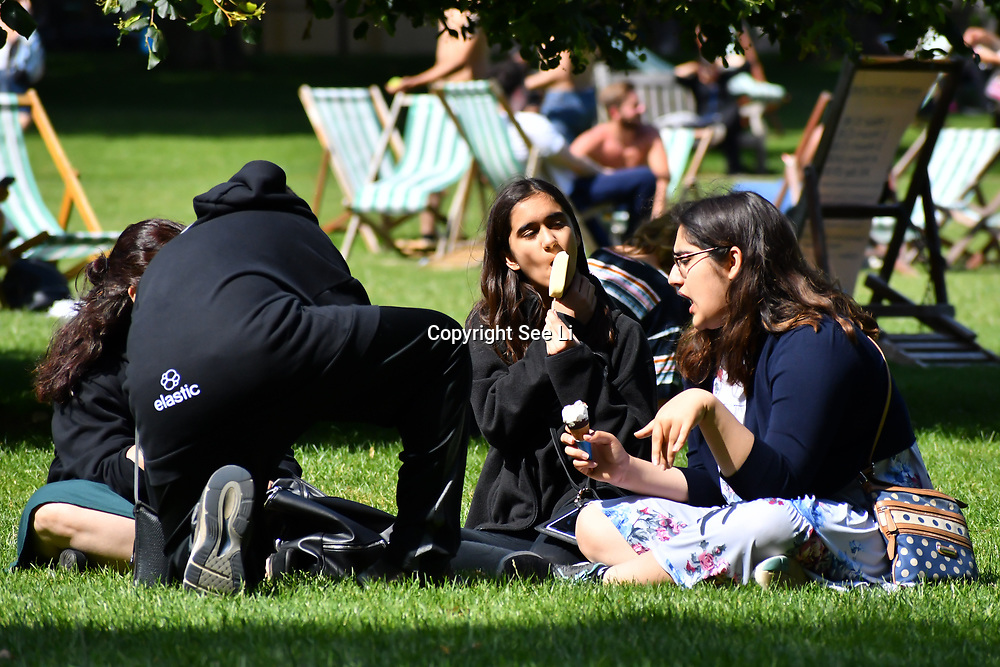 London, UK. 27 June 2019. UK Weather - The Hottest week in June 2019. Young kids eating ice cream at St James park, London, UK