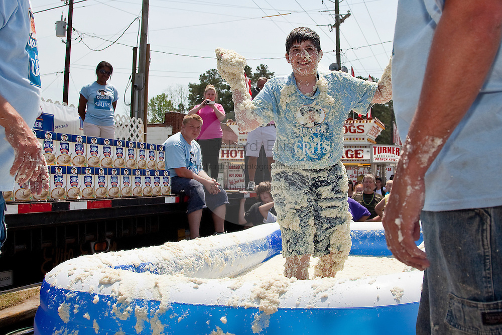 ST GEORGE, SC - APRIL 17: A young boy smiles after rolling around in a giant vat of grits during the World Grits Festival April 17, 2010 in St. George, South Carolina. Among the various events for the festival is the Rolling in the Grits for children where the winner is the one who can hold the most of grits to their body. Grits is corn-based porridge common in the Southern United States.   (Photo Richard Ellis)