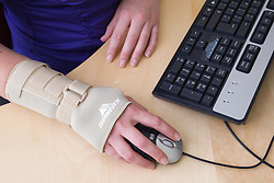 Office worker using a computer mouse whilst wearing an elasticated wrist support to help alleviate repetitive strain injury (RSI); RSI most commonly affects the neck; shoulders; arms and hands of keyboard workers and other people who continually carry out same tasks and movements in their work,