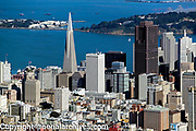 aerial photograph of the San Francisco financial district skyline including the Transamerica pyramid and the Bank of America Center, with Treasure Island in the background