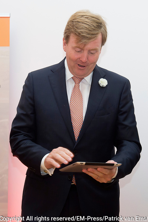 Koning Willem Alexander is bij de lancering van de website  in het Mauritshuis over de restauratie en kunsthistorisch onderzoek Oranjezaal.<br /> <br /> King William Alexander was at the launch of the website in the Mauritshuis on the restoration and art historical research Oranjezaal.<br /> <br /> Op de foto / On the photo:  Koning Willem Alexander verricht de openingshandeling door middel van een swipe over de ipad / King Willem Alexander will host the opening through a swipe across the ipad