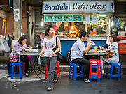 26 MAY 2015 - BANGKOK, THAILAND: A woman walks away from chicken and rice food cart on Sukhumvit Soi 38, one of the most famous street food locations in Bangkok. The food carts and small restaurants along the street have been popular with tourists and Thais alike for more than 40 years. The family that owns the land along the soi recently decided to sell to a condominium developer and not renew the restaurant owners' leases. More than 40 restaurants and food carts will have to close. The first wave of closings could start as soon June 21 and all of the restaurants are supposed to close over the next several months.     PHOTO BY JACK KURTZ