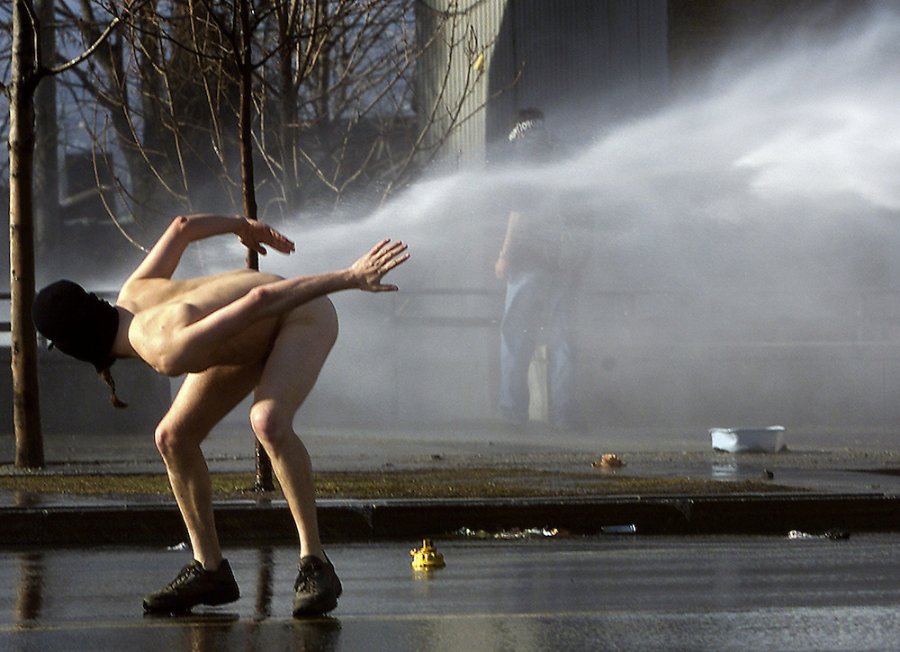 A naked protestor taunts a police water cannon during riots outside the Summit of the Americas in Quebec City April 21, 2001. Police have used plenty of tear gas and rubber bullets to quell rioters outside the Summit.  REUTERS/Jim Young
