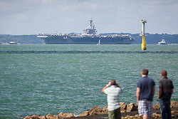 © Licensed to London News Pictures. 01/08/2017. Portsmouth, UK.  People look on as the US Navy Nimitz-Class aircraft carrier, USS George H.W. Bush, departs The Solent for a two-week exercise, Exercise Saxon Warrior 17. The ship has been anchored in Stoke's Bay during her six-day visit to Portsmouth, but is now embarking on a multinational exercise taking place around the UK coast involving five nations, including the US and UK. Photo credit: Rob Arnold/LNP
