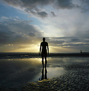 The sun setting behind one of the bronze statues of Antony Gormley's Another Place installation at Crosby, Merseyside at the mouth of the river Mersey. The Mersey is a river in north west England which stretches for 70 miles (112 km) from Stockport, Greater Manchester, ending at Liverpool Bay, Merseyside. For centuries, it formed part of the ancient county divide between Lancashire and Cheshire.