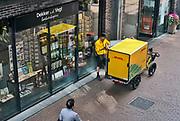 Nederland, Nijmegen, 30-4-2020 Een medewerker van pakketbedrijf DHL levert bestellingen af aan een boekhandel in een winkelstraat. Hij heeft een speciale fiets , vrachtfiets met aanhanger die het bezorgen in de bnnenstad, stadscentrum, voetgangersgebied, autovrije straat, makkelijker maakt . Door de coronacrisis worden er meer online bestellingen gedaan die  . Shoppen .Foto: Flip Franssen