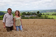 British small organic farming couple in a field in front of their farmhouse, Higher Hacknell farm, Dartmoor, Devon, UK food industry
