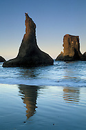 Jagged rocks and ocean surf waves on coastal beach at dawn, Bandon State Beach, Bandon, Oregon