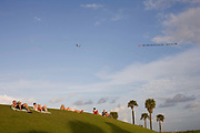 People relaxing reading sleeping and chilling out in South Point Park South Beach Miami which was redeveloped and reopened in 2009. Above them in the sky an aeroplane tows a long  banner advertising a local nightclub