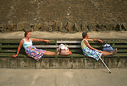 Sisters sit in identical poses on sea wall benches on Blackpool's Promenade.