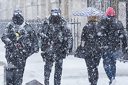 Armed police officers patrol on Whitehall as a sudden, intense snow flurry hits Westminster at Horseguards. Westminster, London, February 27 2018.