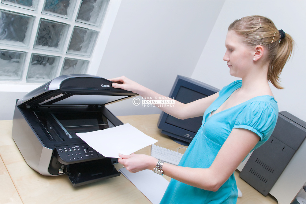 Teenaged girl on work experience placement from school doing some photocopying in the work place,