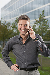 Smart businessman speak a cell phone standing in front of an office building, Bavaria, Germany