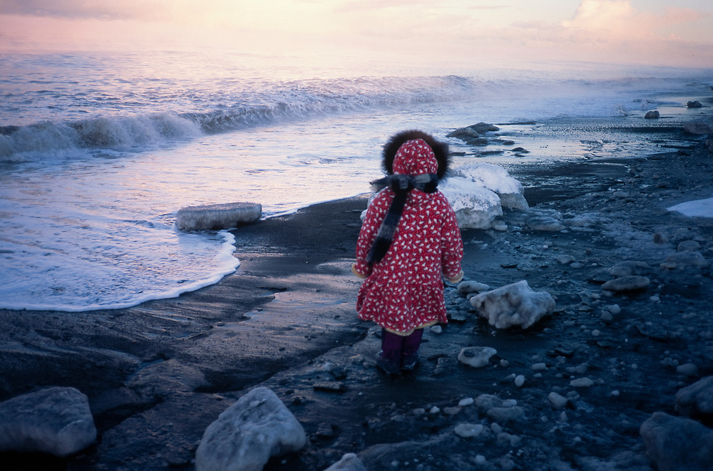 Alaska. Barrow. Young native girl stands at the edge of the Beaufort Sea.