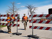 """26 APRIL 2020 - DES MOINES, IOWA: Soldiers with the Iowa Army National Guard open the gate of the COVID-19 drive through testing site in Des Moines. Iowa started mass testing Saturday, with a drive through testing site in a parking lot in downtown Des Moines. The testing this weekend is considered a """"soft opening"""" for the program and tests were reserved for medical professionals and first responders. Despite numerous outbreaks in meat packing plants throughout Iowa, members of the public have not been able to get tested. On Saturday, 25 April, there were 5,092 confirmed cases of COVID-19 (Coronavirus / SARS-CoV-2) in Iowa (an increase of 647 since Friday, April 24) and 112 deaths in Iowa caused by COVID-19.PHOTO BY JACK KURTZ"""
