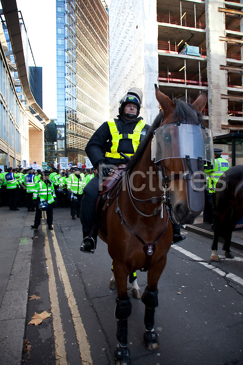 """Police horses in riot gear are deployed in The City of London along New Fetter Lane as students march through central London to protest against rises in tuition fees and changes to higher education. The police were out in force as thousands of students marched through central London. Some 4,000 officers were on duty, as demonstrators marched peacefully in a protest against higher tuition fees and """"privatisation"""" in universities. The police estimated that about 2,000 people took part in the demonstration."""